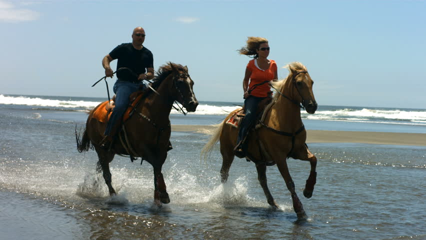 Couple riding horses on beach, slow motion | Shutterstock HD Video #4578962