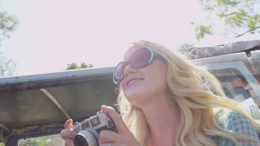 Young woman taking photos with vintage camera on road trip