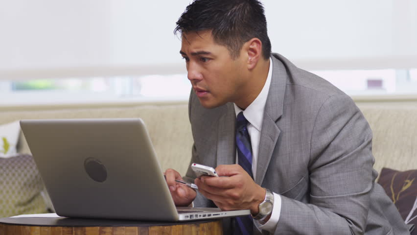 Business man in office lobby using laptop and cell phone | Shutterstock HD Video #4584770