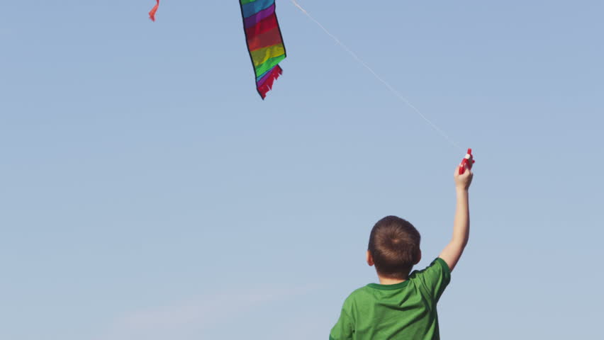 Young boy flying kite, slow motion