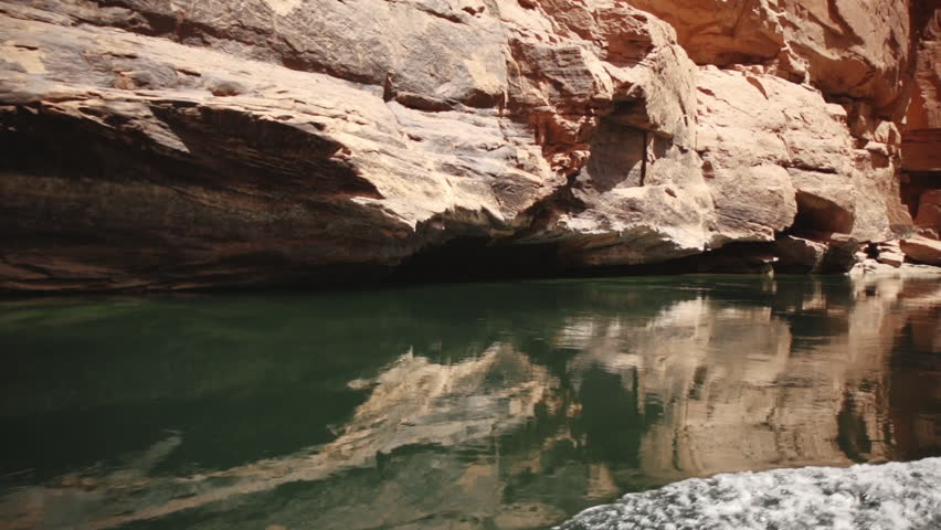 Rafting by the walls of the Grand Canyon creating ripples in the green water of the Colorado River.