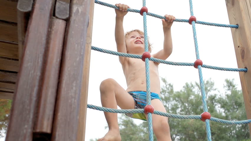 Slow Motion Of A Cute Boy Climbing Up A Rope Ladder Outdoors On The Playground.