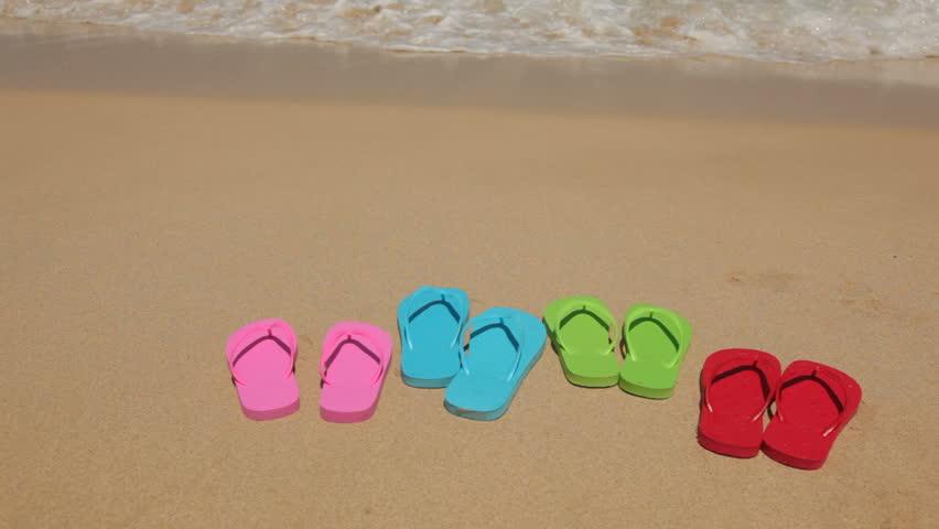 Family's sandals on sandy beach