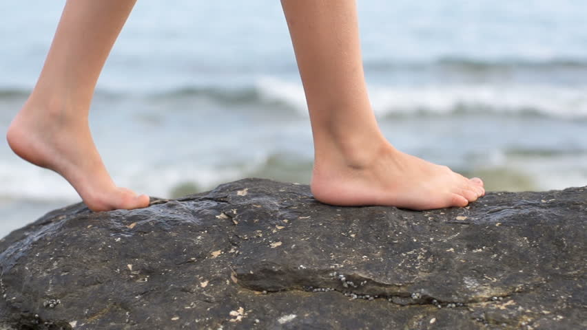 Slow Motion Shot Of A Child's Bare Feet Walking On Seaside Rocks With Ocean In