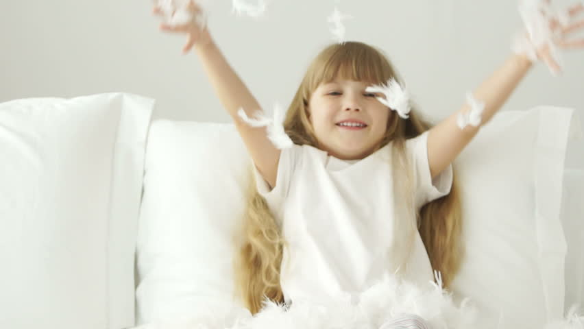 Funny little girl playing with pillow feathers and laughing