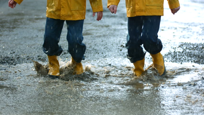 Two young boys jumping in mud puddle