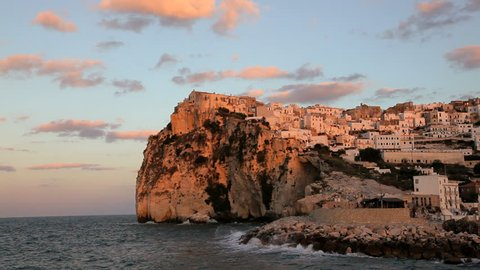 Scenic view of Adriatic tide breaking against the sea wall of the historic town Peschici on a rocky cliff in the National Park of Gargano, Promontorio Del Gargano, Puglia, Italy