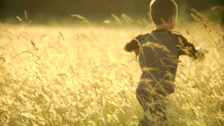 A boy runs through a field of grass.