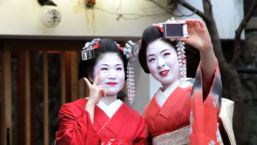 Japan - March 2011: Two Japanese Geishas taking pictures of themselves and waving in the street in Japan in March, 2011