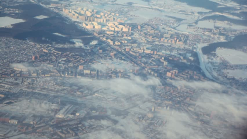Landscape with fields and big city covered by snow, view from plane during flight