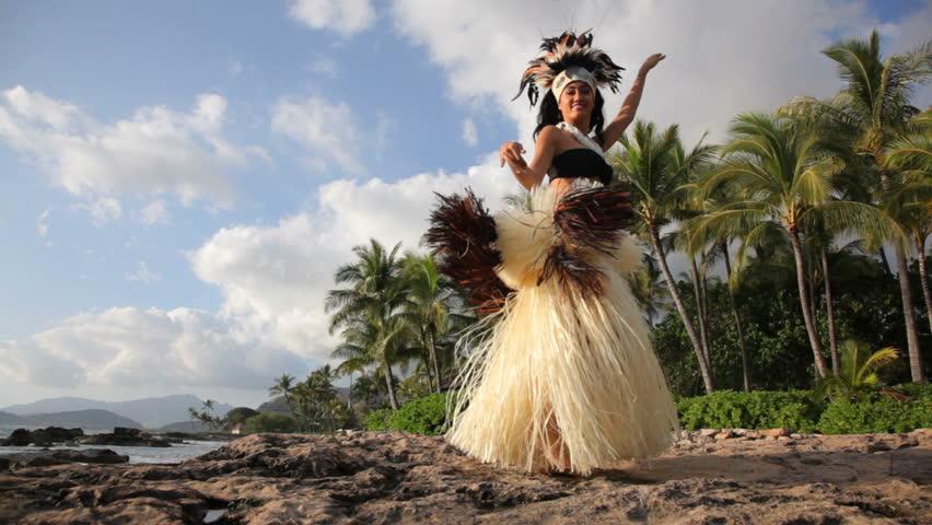 Polynesian dancer performs along rocky coastline