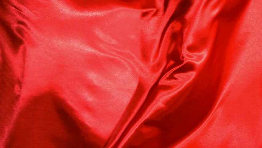 Red satin fabric blowing in the wind, abstract background