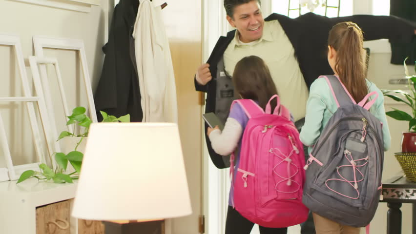 A father and his two daughters get ready and leave for school in the morning. Medium shot.
