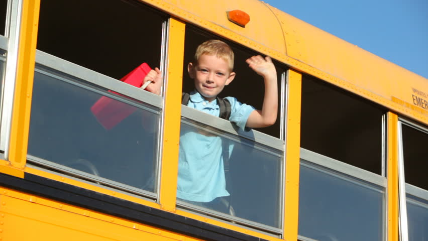 Young boy waves out window of school bus
