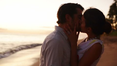 A silhouetted couple hold each other and kiss on the beach. The tide massages their feet at dusk, the golden hour