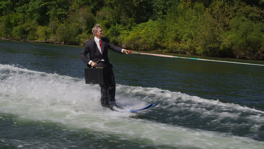 Businessman with briefcase water skiing to work, slow motion