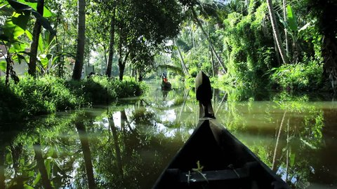 India - January 2011: Traditional local canoe passing people and isolated rural villages along a tropical river in Alleppey, Kerala India in January, 2013
