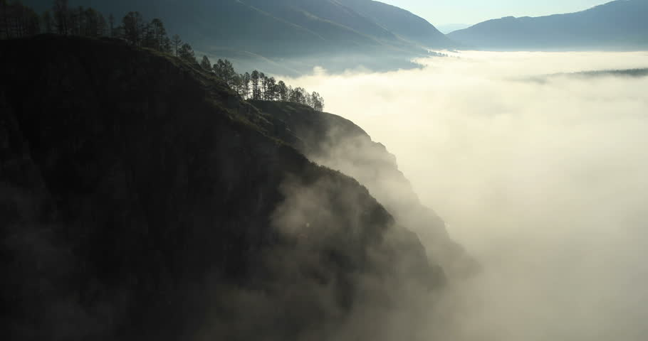 Aerial View. Flying over the high mountains in beautiful clouds . Aerial camera shot.  Air clouds. Altai, Siberia. #4669151
