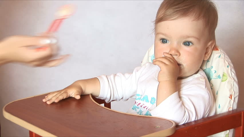 Baby sits at a children's little table. Mum feeds the child with porridge. Isolated on the white