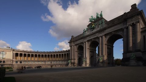 Brussels Triumphal Arch monument at Cinquantenaire park. Photo time-lapse in the afternoon, featuring the arch, one of two colonnades, pedestrians and clouds (Belgium, 2012 Oct).