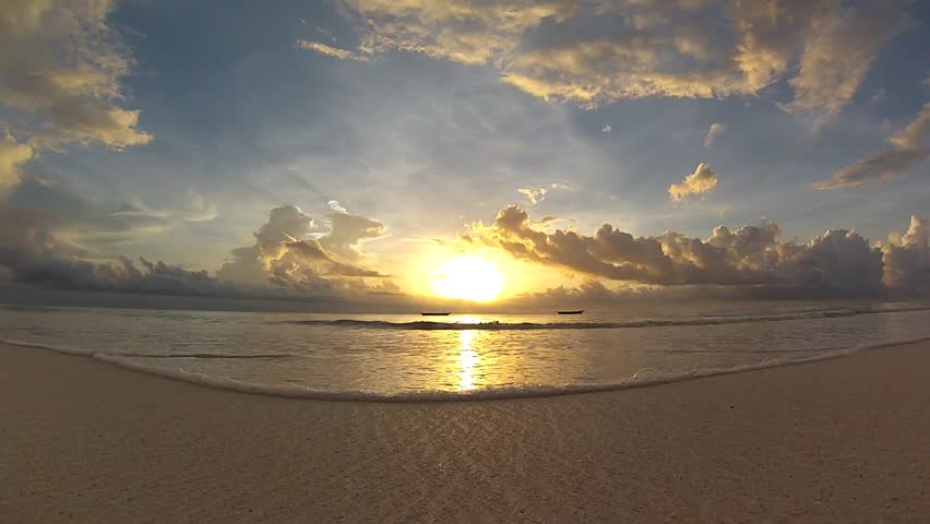 The sun rises over a beautiful beach in Africa as waves wash across the sand. #4686377