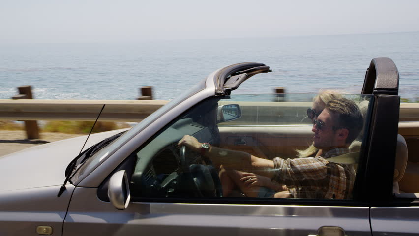 Couple driving convertible together along beach