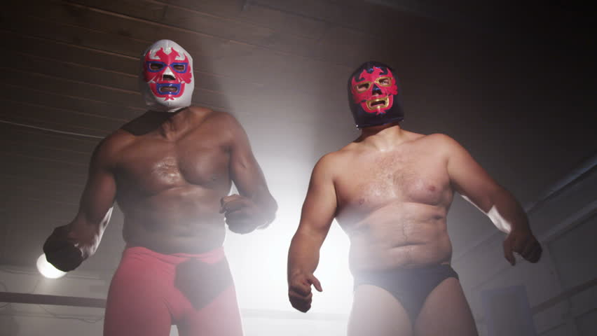 Two masked wrestlers intimidating opponent