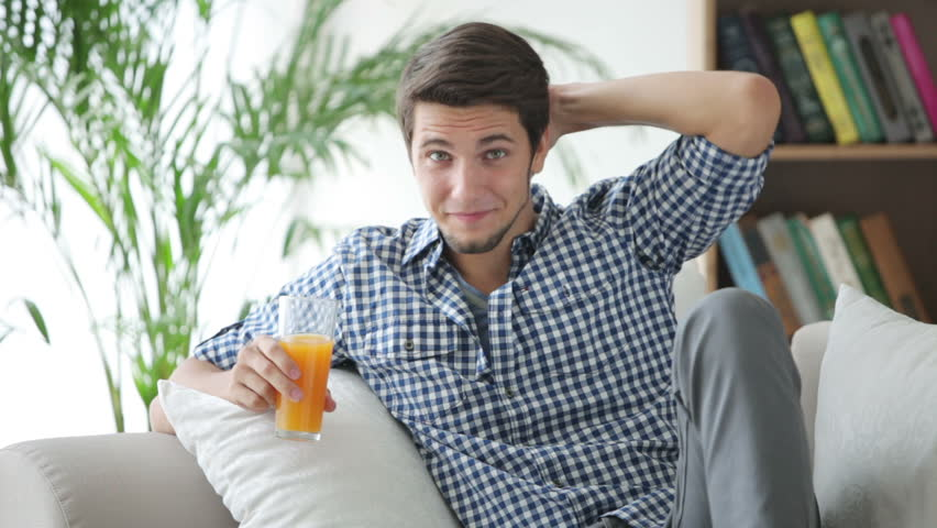 Charming guy sitting on sofa holding glass of juice and smiling