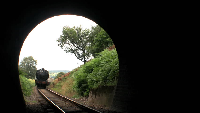 Steam train entering tunnel