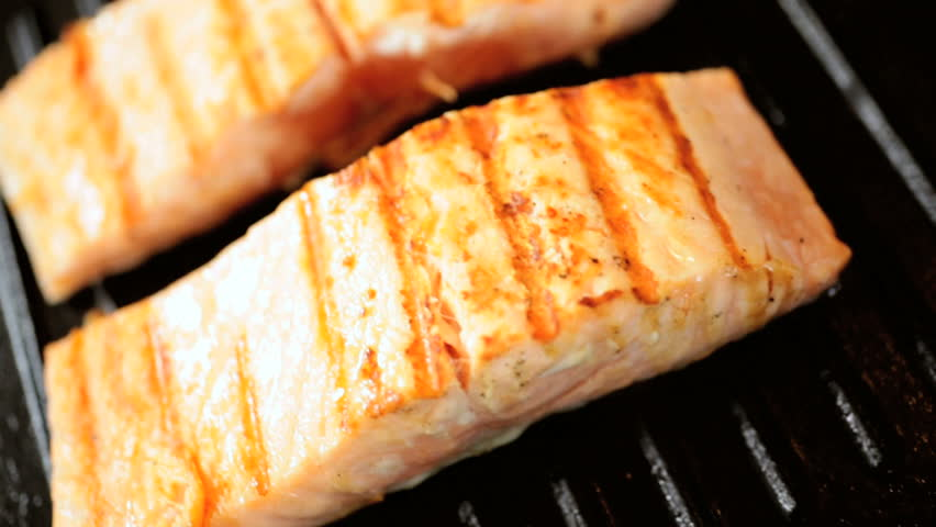Fresh salmon steaks with grill marks cooking for a healthy nutritious family meal