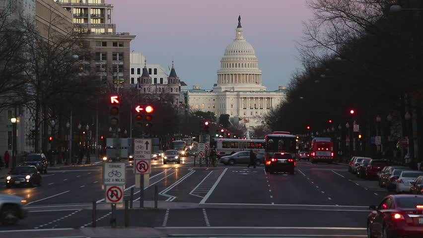 Time lapse footage at dusk looking down to the illuminated US Capitol building on Pennsylvania Avenue with pedestrians and traffic in foreground, Washington DC