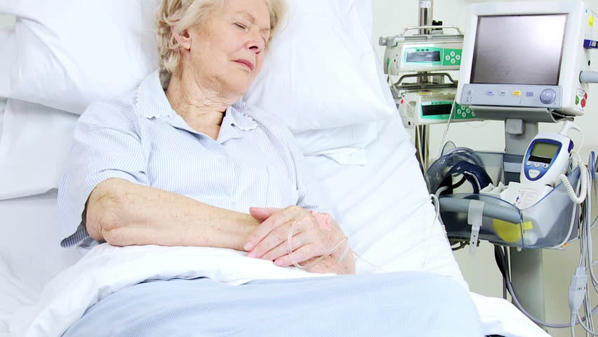 Elderly female Caucasian lady sleeping in a hospital bed recoverying from illness