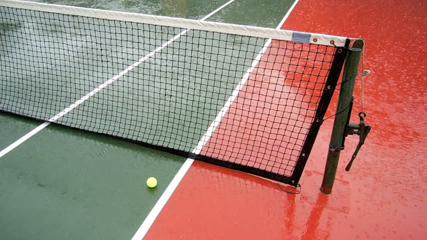 Rain falling on tennis court with a ball sitting near the net