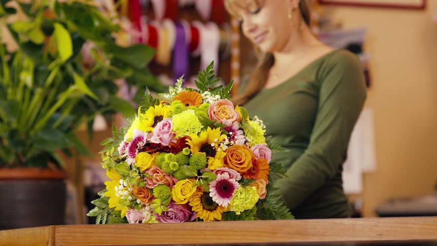 young hispanic woman working as florist in flower shop and looking at camera, smiling with bouquet on desk