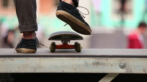 Legs of skateboarder which star ride on board from ramp