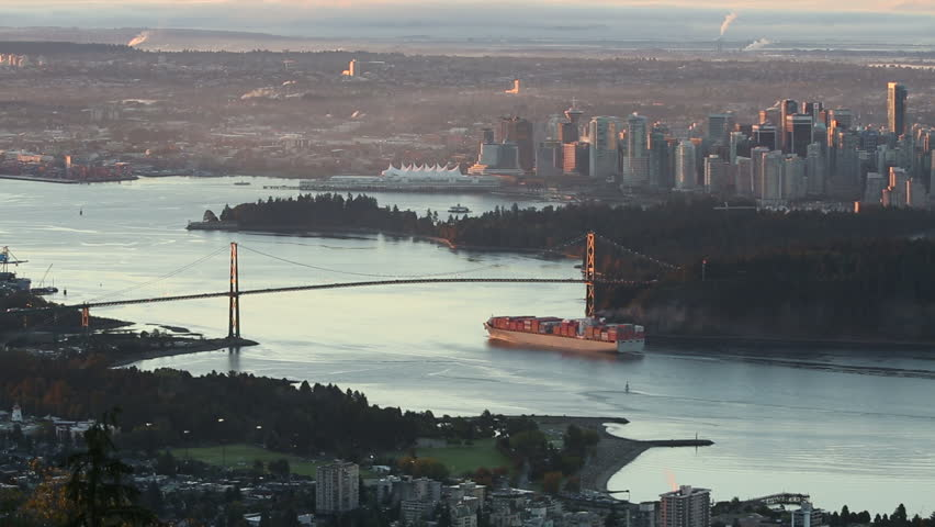 A high angle view of downtown Vancouver, the Lions Gate Bridge, and Burrard Inlet at sunrise. A freighter passes under the bridge as the sun comes up. British Columbia, Canada.
