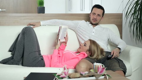 Couple gets bored of watching TV and reading a book, and they start kissing. High definition video.