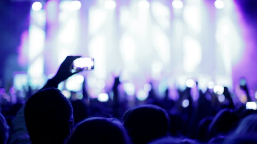 Crowd making party at a rock concert. Hands hold cameras with digital displays among people at rock concert