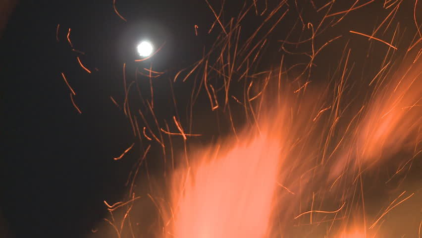 A night time fire sends flames into the air with a full moon visible in the