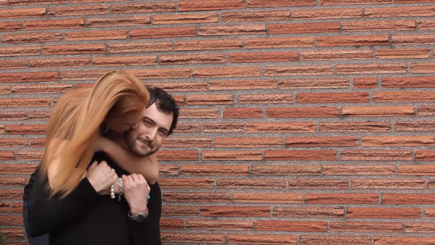A young couple hug and kiss while standing in front of a brick wall