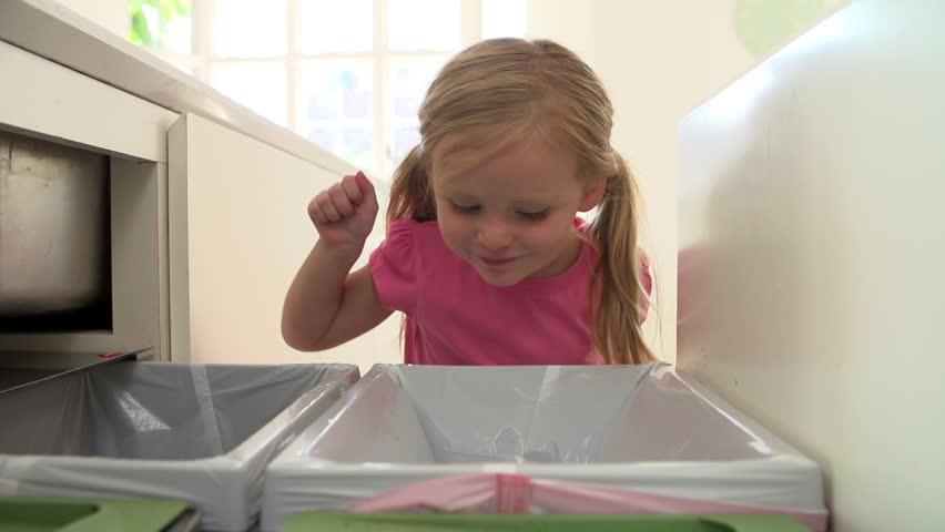 Girl drops plastic bottle into kitchen recycling bin in slow motion