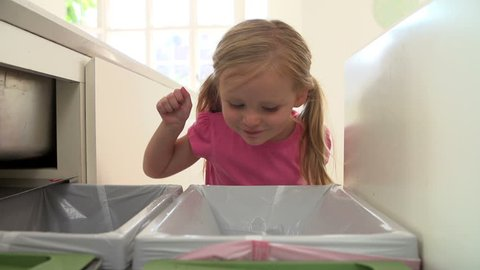 Girl drops plastic bottle into kitchen recycling bin in slow motion