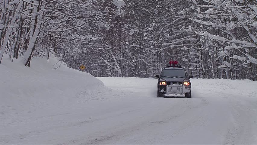 A car travels on a snowy mountain road.