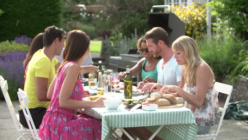 Group Of Young Adult Friends Enjoying Summer Barbecue On Backyard Patio