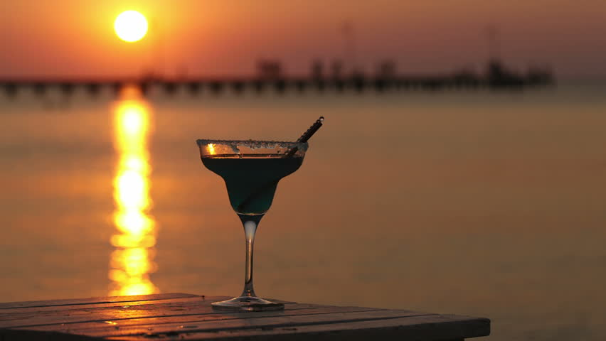 Glass of tropical cocktail standing on a wooden table overlooking a sunset ocean with the setting sun casting a fiery path across the water