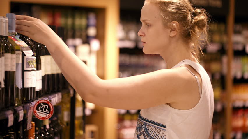 Woman shopping for wine or other alcohol in a bottle store standing in front of shelves full of bottles with a serious expression as she tries to make up her mind | Shutterstock HD Video #4882661