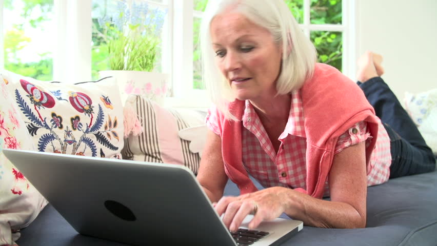 Middle aged woman lying on sofa and using laptop computer