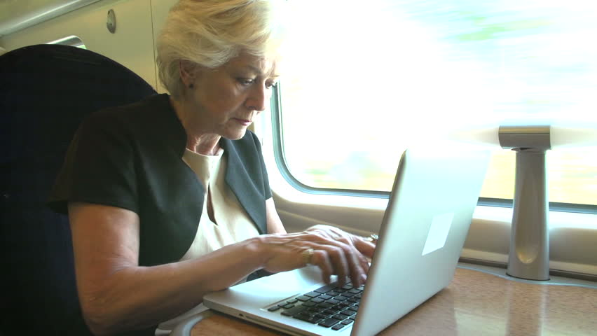Senior businesswoman working intently on laptop computer on train journey - HD stock footage clip