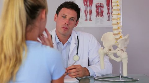 Chiropractor speaking with his patient and explaining something using spine model