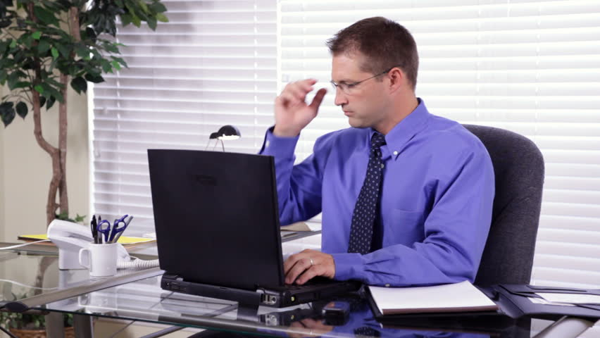 A young, attractive, happy, businessman working at his desk takes a phone call and makes notations on a notepad.